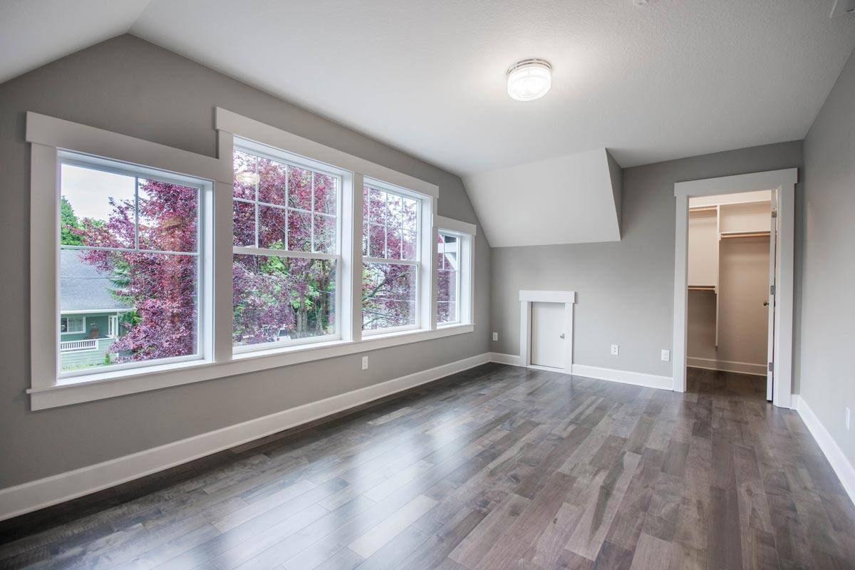 Spacious primary bedroom with hardwood flooring and white paneled windows. A door on the side opens to the walk-in closet.