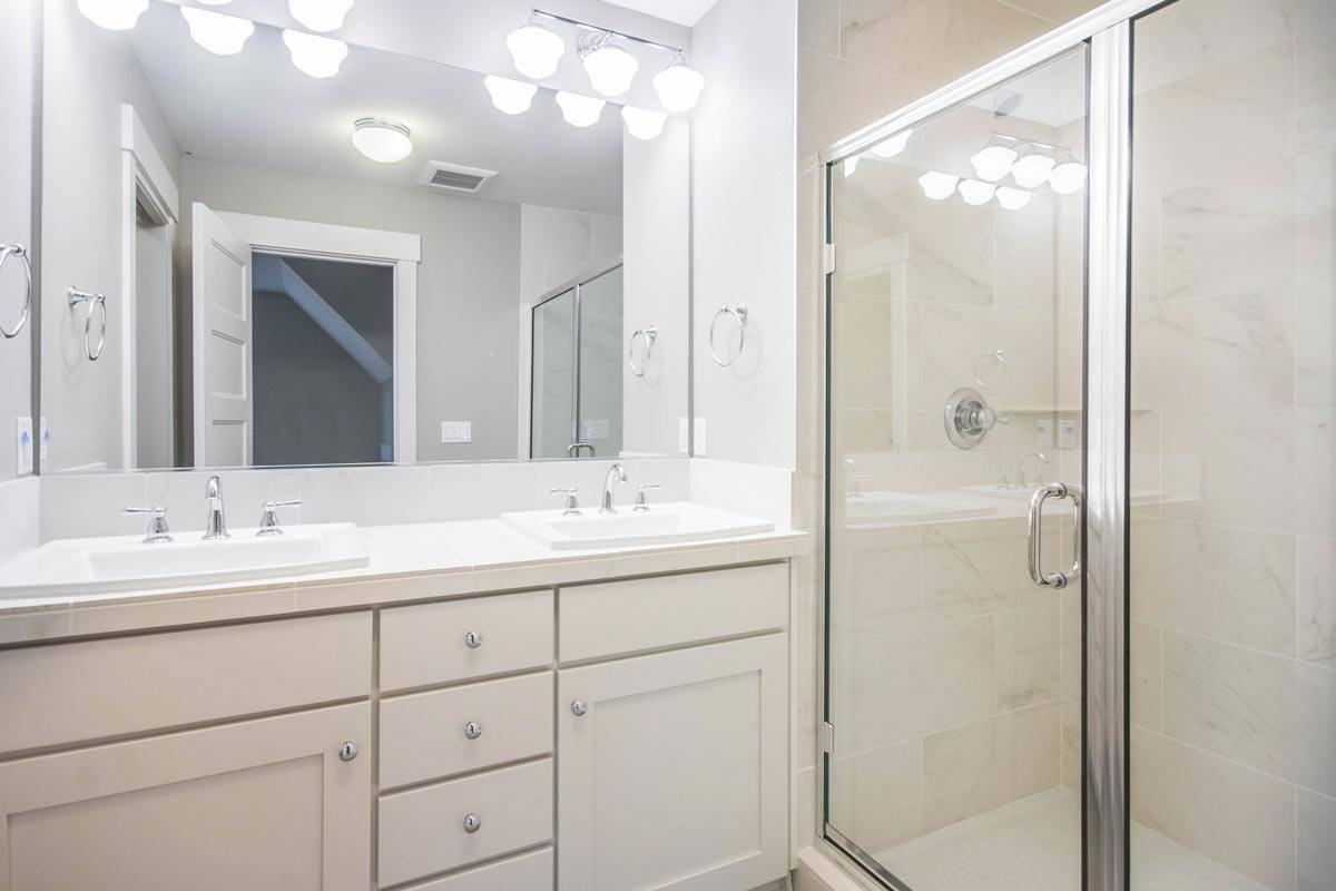 Primary bathroom with a shower area and a dual sink vanity paired with a large frameless mirror.