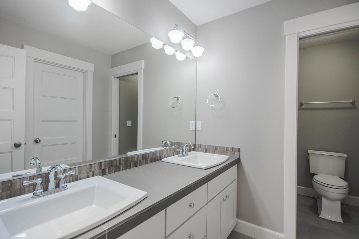 This bathroom is equipped with a toilet room and a vanity with dual sink and a gray countertop.