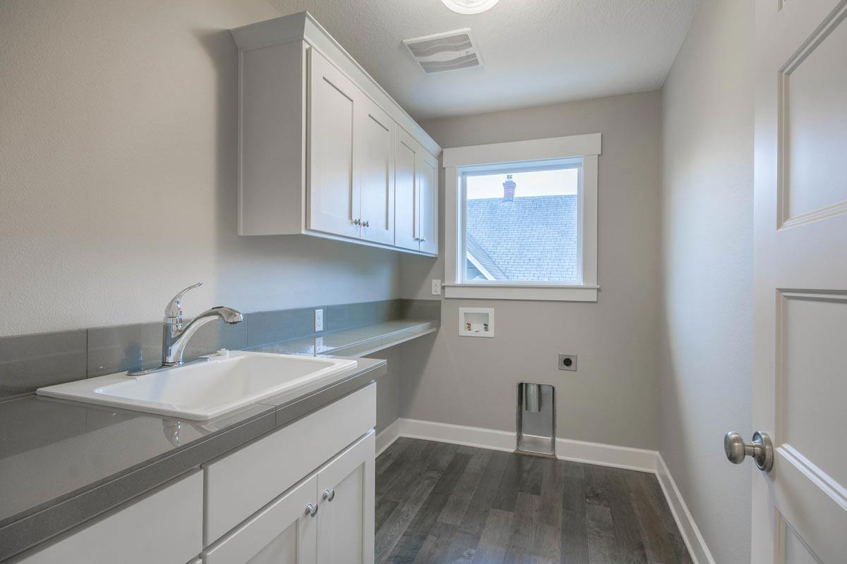 Utility room with a picture window, white cabinets, and a porcelain sink fitted on the granite countertop.