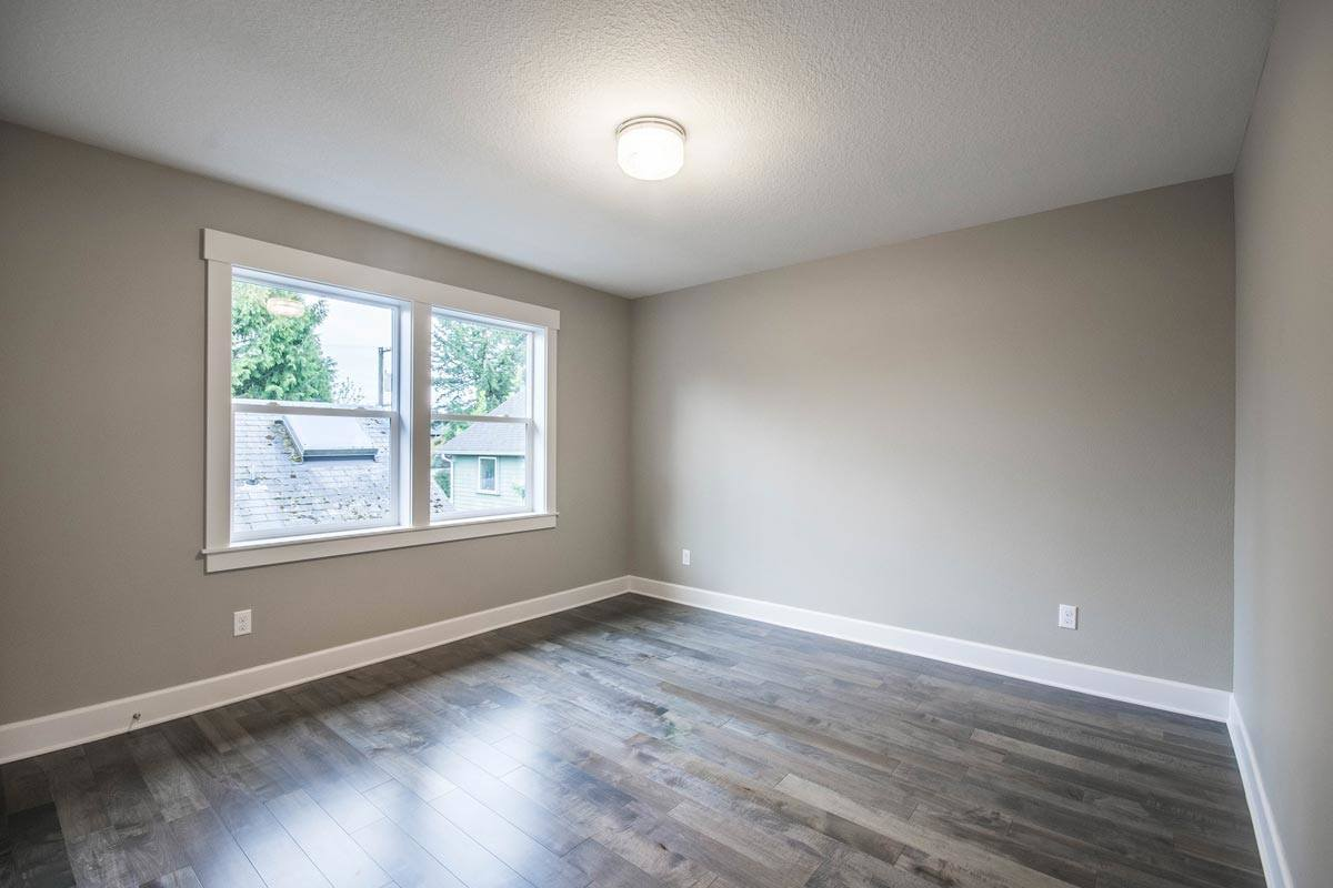 Another bedroom with gray walls, natural hardwood flooring, and white framed windows.