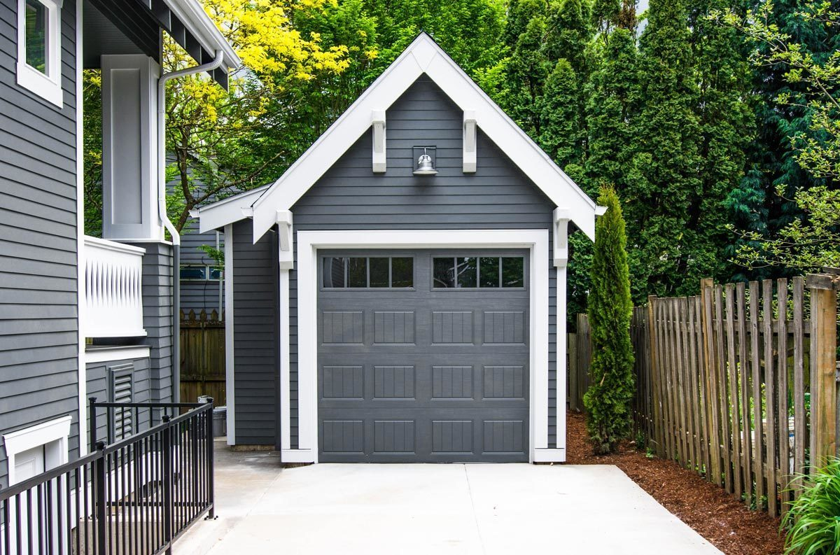 A detached garage situated at the back of the house. It has a gable roof, horizontal exterior siding, and a large gray door.