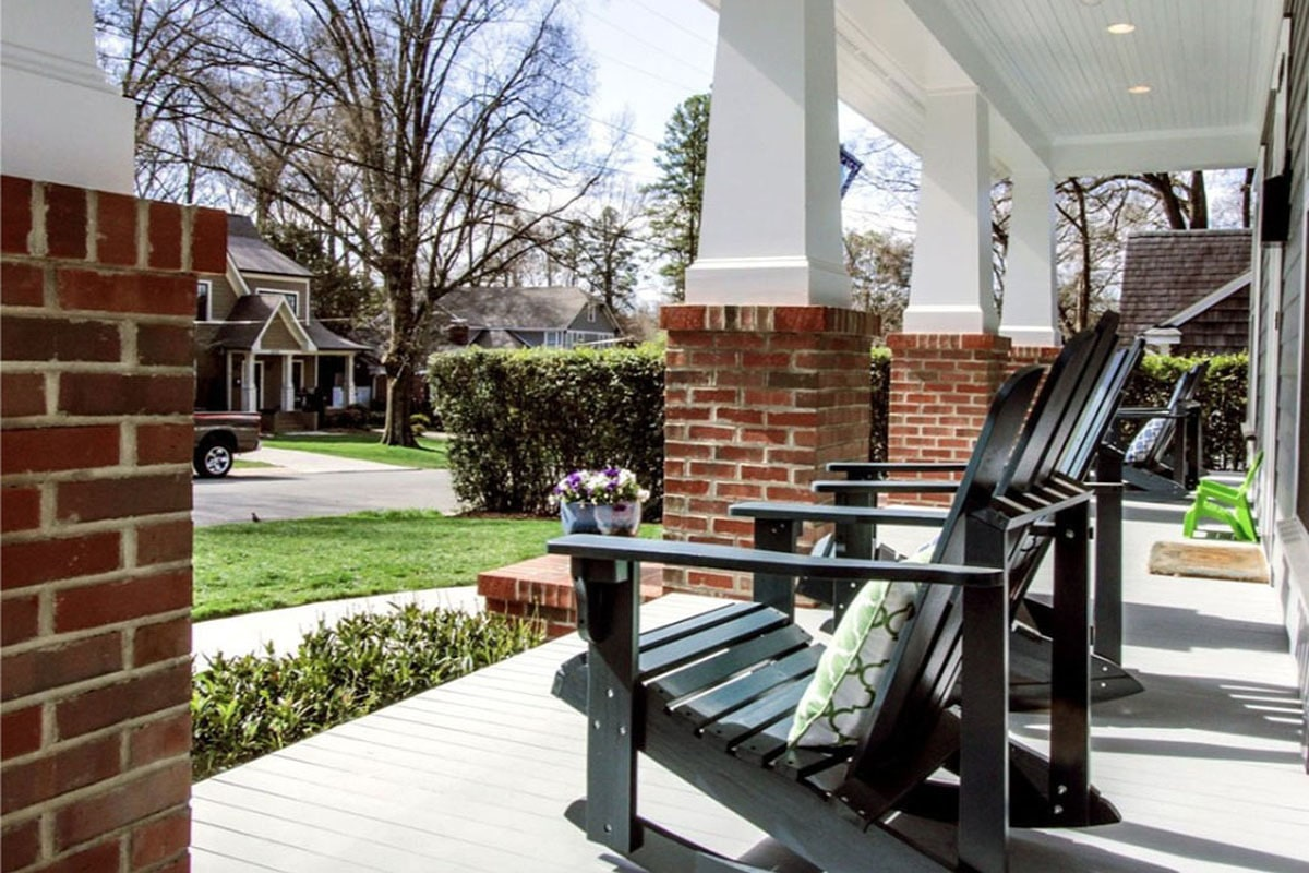 Black rocking chairs accented with patterned pillows fill the front porch overlooking the serene surrounding.
