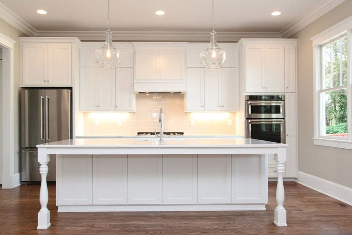 The kitchen is equipped with stainless steel appliances, white cabinetry, and an undermount sink fitted on the center island.