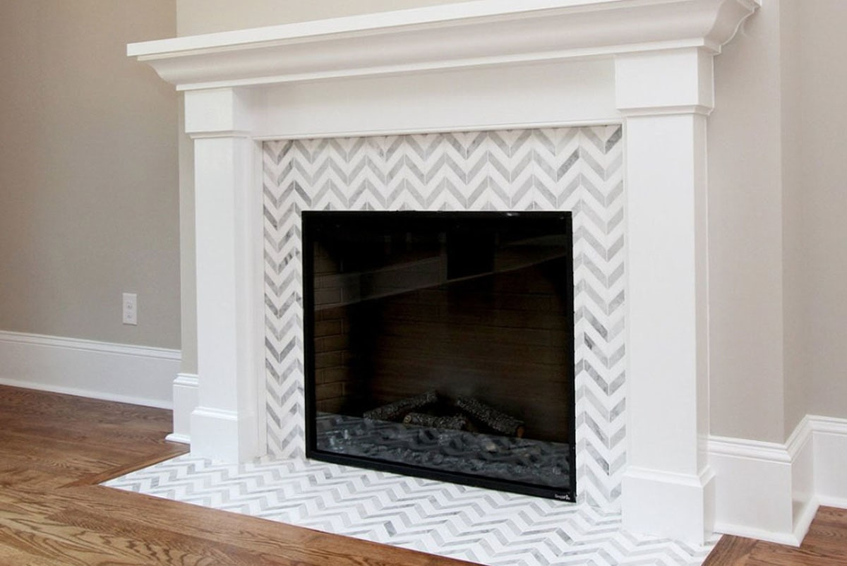 A closeup look at the glass-enclosed fireplace bordered with striking chevron tiles.