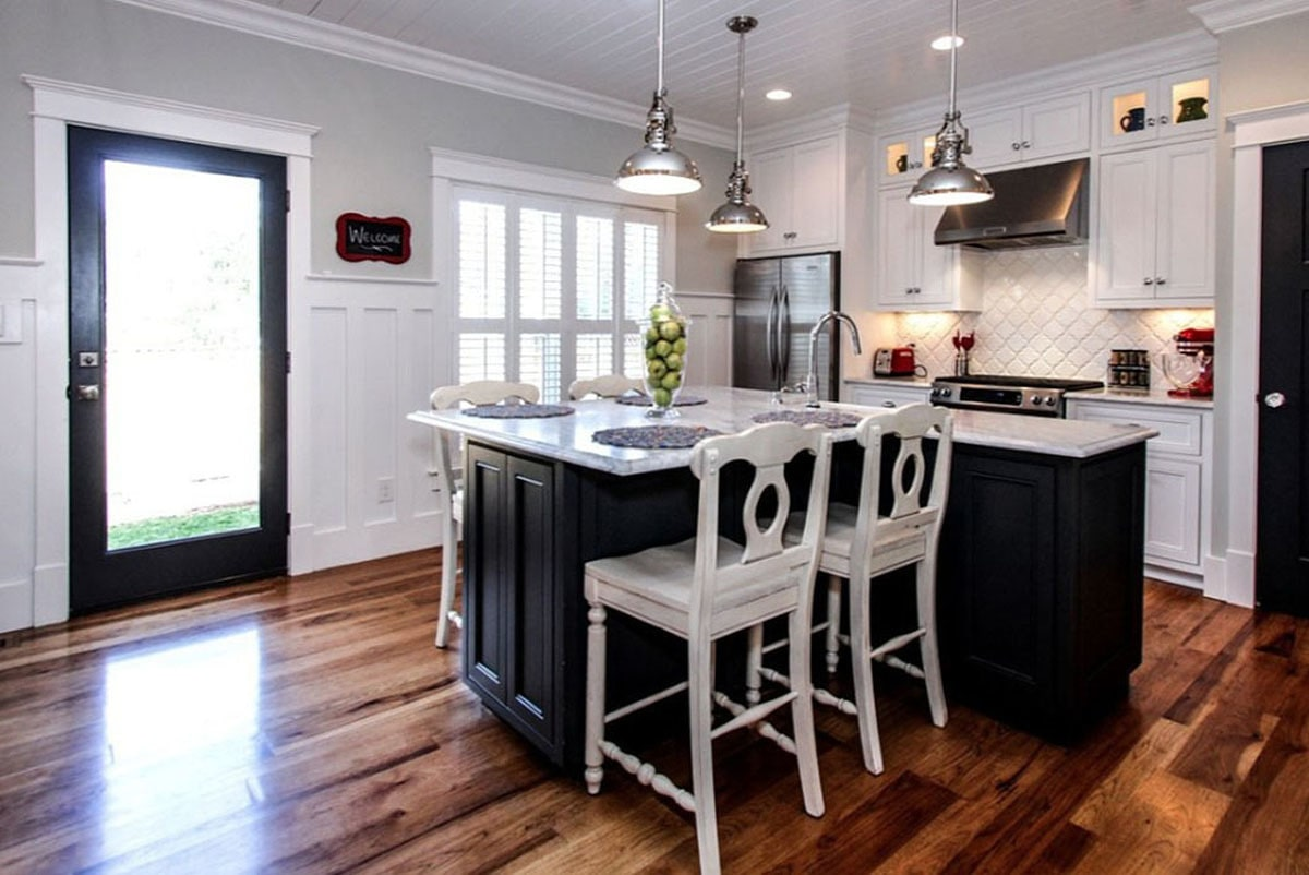 This kitchen offers white cabinets and an L-shaped breakfast island complemented with distressed counter chairs and chrome dome pendants.