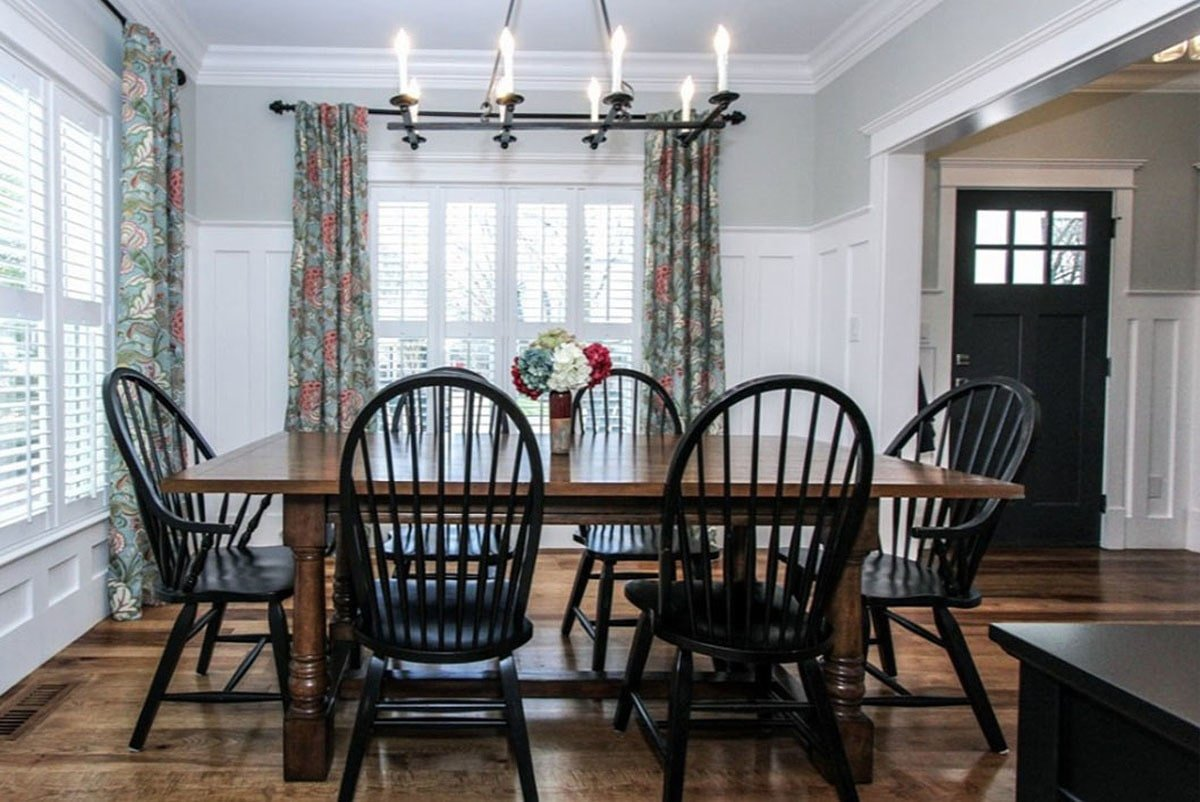 Formal dining room with round back chairs and a wooden dining table illuminated by a candle chandelier.