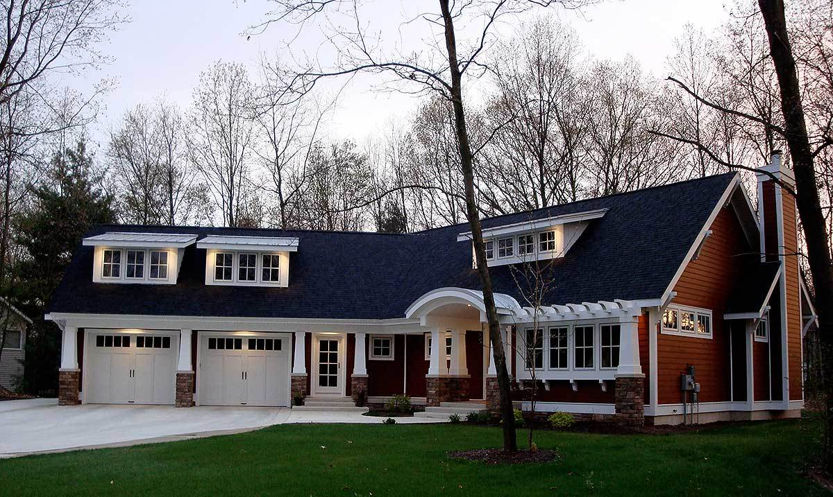 Home's front view showing the red exterior siding, charming dormers, and an angled two-car garage.
