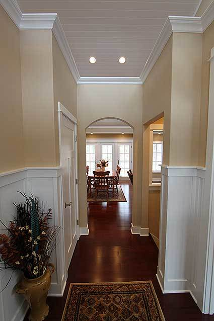 Entry hallway with a large vase, patterned rug, and an archway that opens to the main living space.