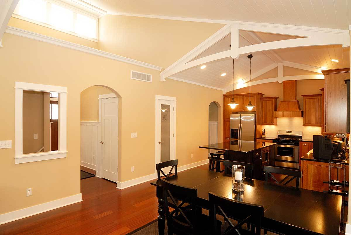 The dining area offers a rectangular dining table and matching black chairs sitting on a bordered area rug.