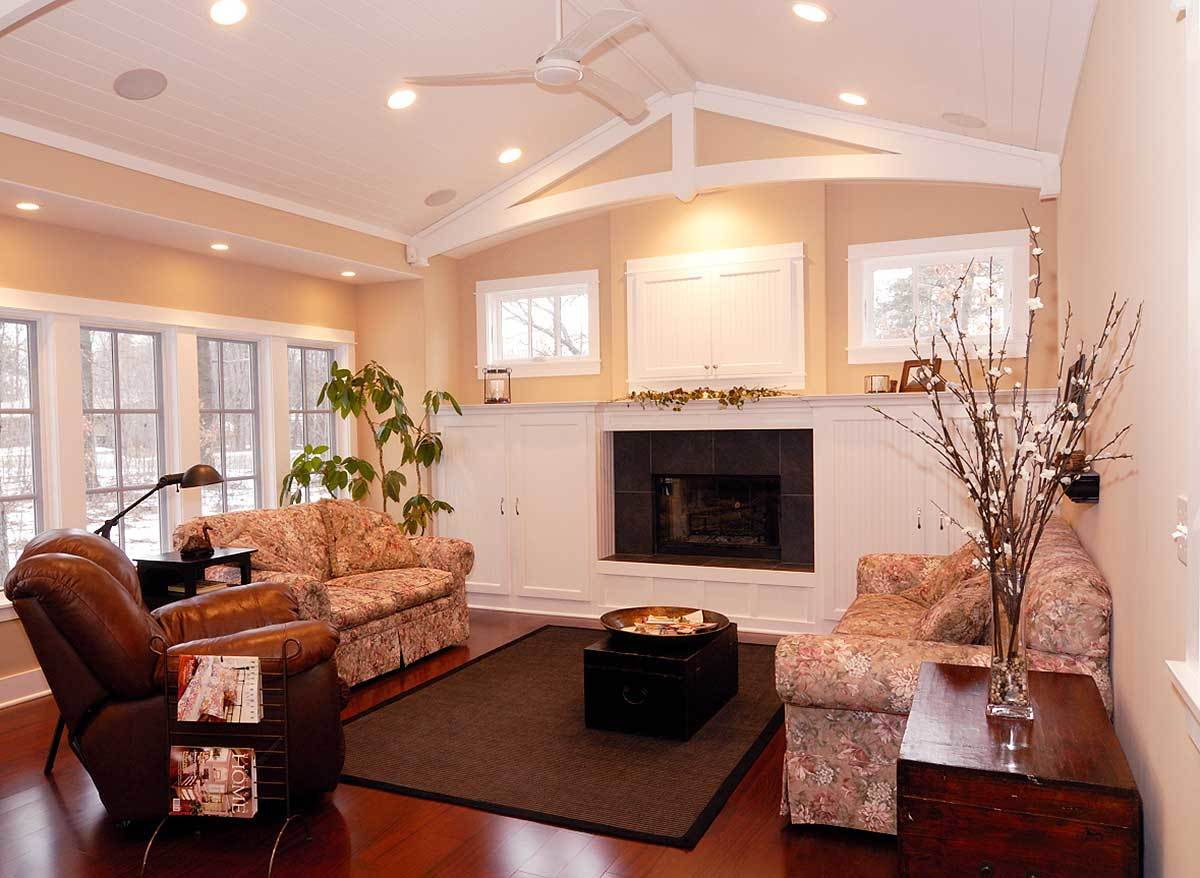 The living room has a rich hardwood flooring, a glass-enclosed fireplace, and a white vaulted ceiling mounted with a fan and recessed lights.
