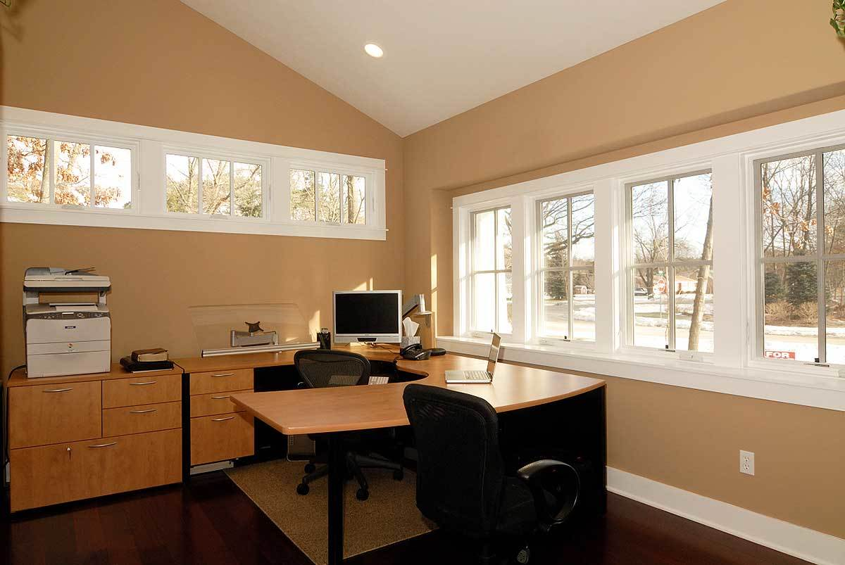 The study is furnished with wooden cabinets, a custom L-shaped desk, and black swivel chairs.