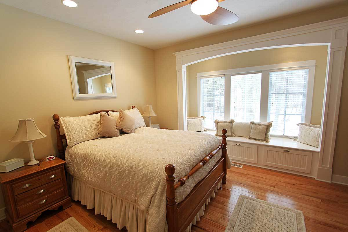 Primary bedroom with wooden furnishings, small bordered rugs, and a window seat nook filled with fluffy pillows.