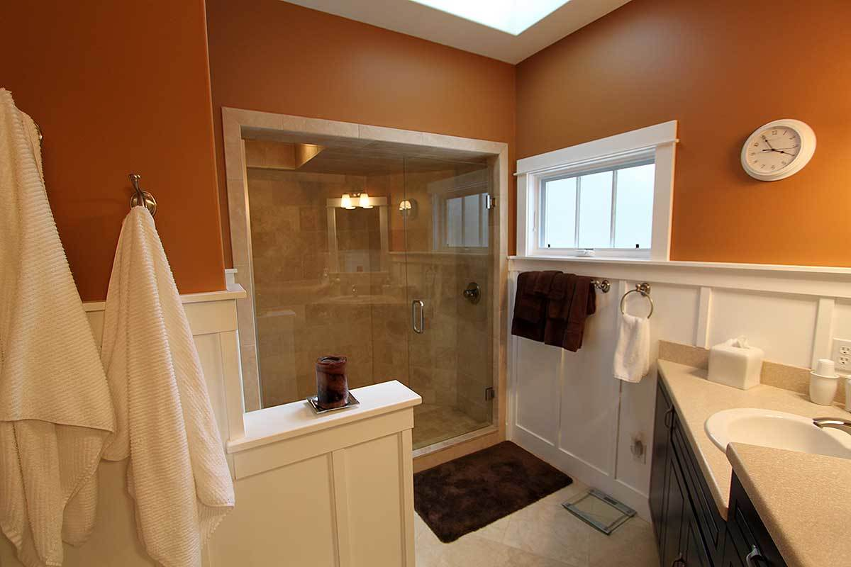The primary bathroom is equipped with a walk-in shower, sink vanity, and a toilet concealed in a white half wall.