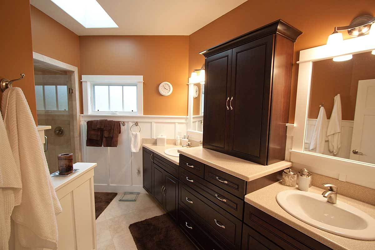 A farther view shows the lengthy vanity topped with a dual sink and a dark wood cabinet.
