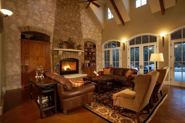 The living room offers brown leather sofas, beige wingback chairs, and a wooden coffee table facing the warm fireplace.
