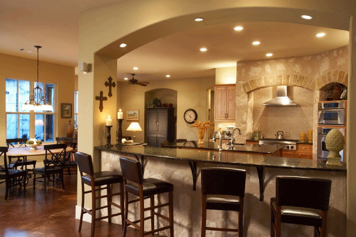 Eat-in kitchen with wooden cabinets, a center island, and a granite top peninsula lined with black leather counter chairs.