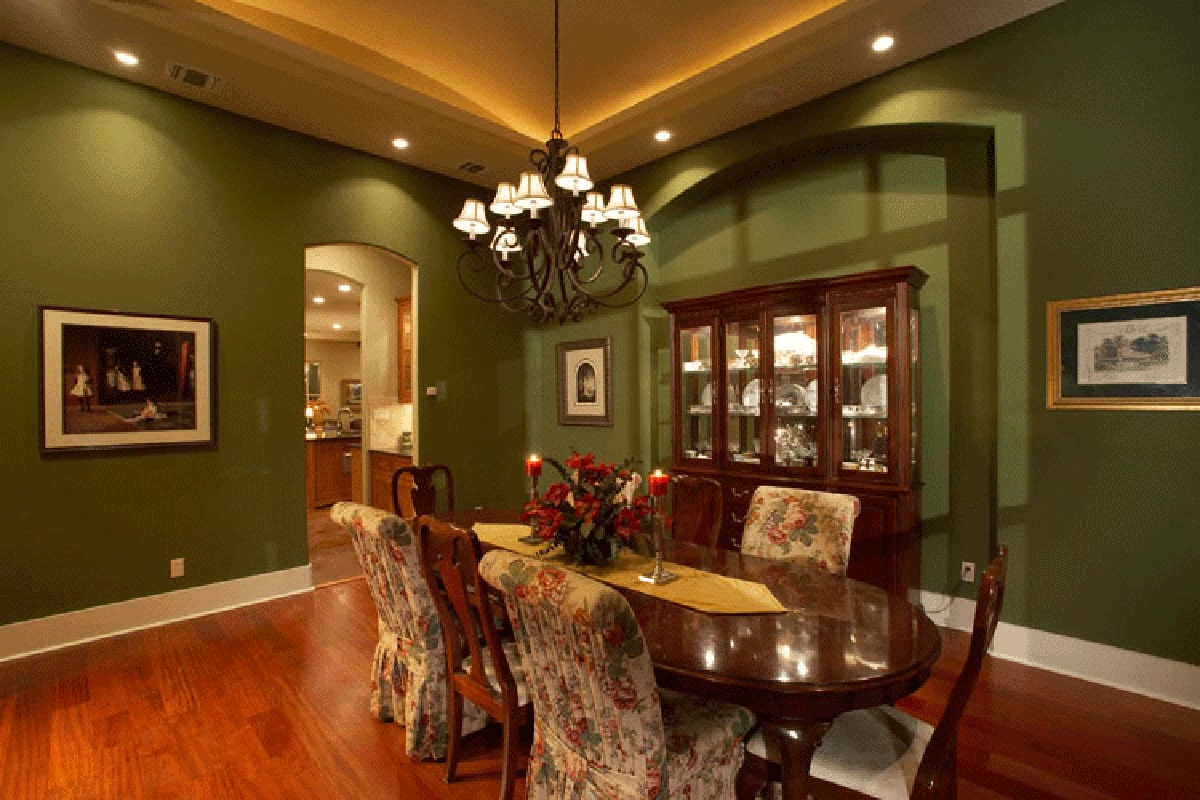 Formal dining room with emerald green walls and a glowing tray ceiling mounted with a wrought iron chandelier that hangs over the oval dining set.