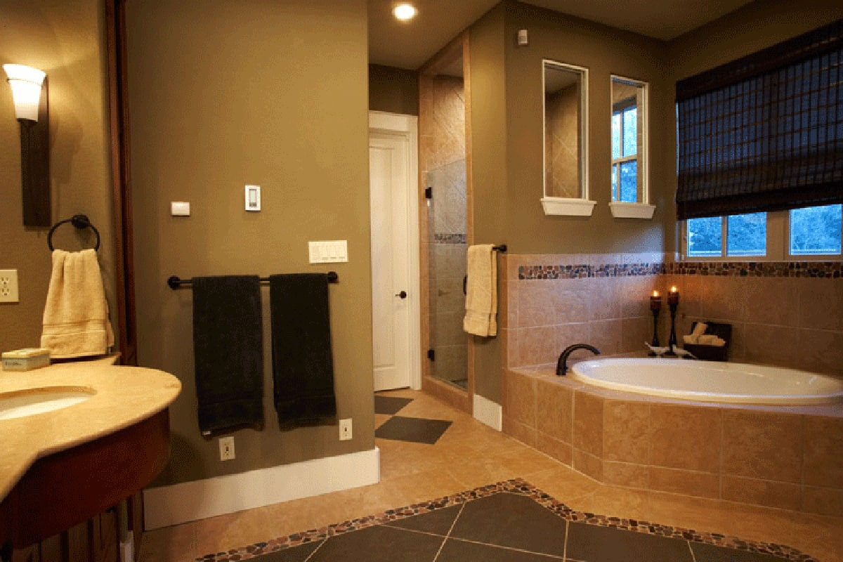 Primary bathroom equipped with a walk-in shower, a sink pedestal, and a deep soaking tub clad in beige marble tiles.