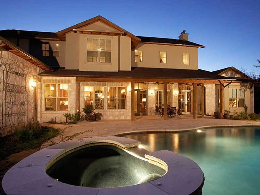 Home's rear view showing the covered lanai and a dazzling pool integrated with a relaxing spa.
