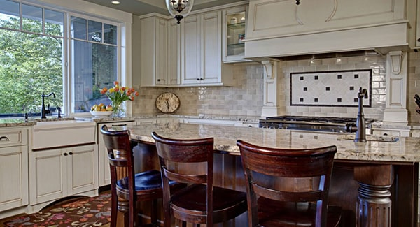 The kitchen is equipped with white cabinets, a farmhouse sink, and an island bar fitted with another sink.