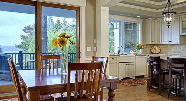 The breakfast nook offers wooden chairs and a square dining table topped with a glass vase.