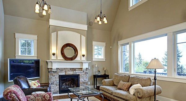 The living room has cozy seats, a glass top coffee table, warm chandeliers, and a stone fireplace with a round mirror on top.