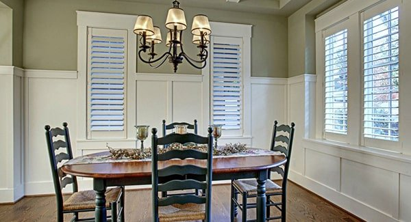 Formal dining room with an oval dining set, hardwood flooring, and gray walls adorned with white wainscoting.