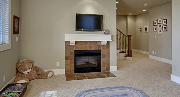 The recreation room offers a wall-mounted TV, a tiled fireplace, and an oval rug that lays on the beige carpet flooring.