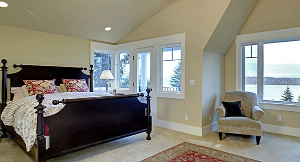 Primary bedroom with a vaulted ceiling and lots of white framed windows that invite an ample amount of natural light in.