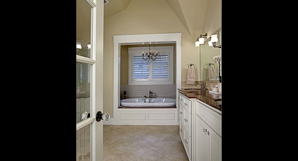 A glass door opens to the primary bathroom with large sink vanity and a deep soaking tub lit by a wrought iron chandelier.