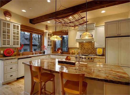 The kitchen is equipped with white cabinetry, granite countertops, hanging wine glass rack, and a center island paired with cushioned bar chairs.