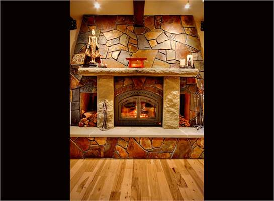A magnificent stone fireplace with arched glass door and a stone mantel.