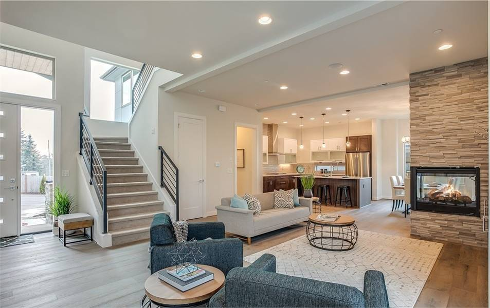 The living room has sweeping views of the two-story foyer along with the warm kitchen and dining.