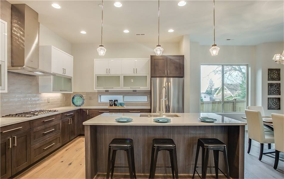 The kitchen is equipped with white and dark wood cabinets, stainless steel appliances, and a center island illuminated by glass pendants.