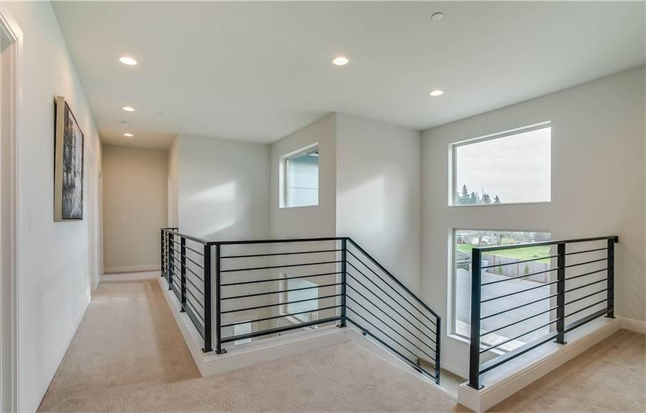 Second-floor balcony with beige carpet flooring and sleek wrought iron railings.