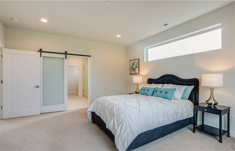 The primary bedroom has a cozy upholstered bed, black nightstands, and a frosted glass barn door that opens to the private bath.