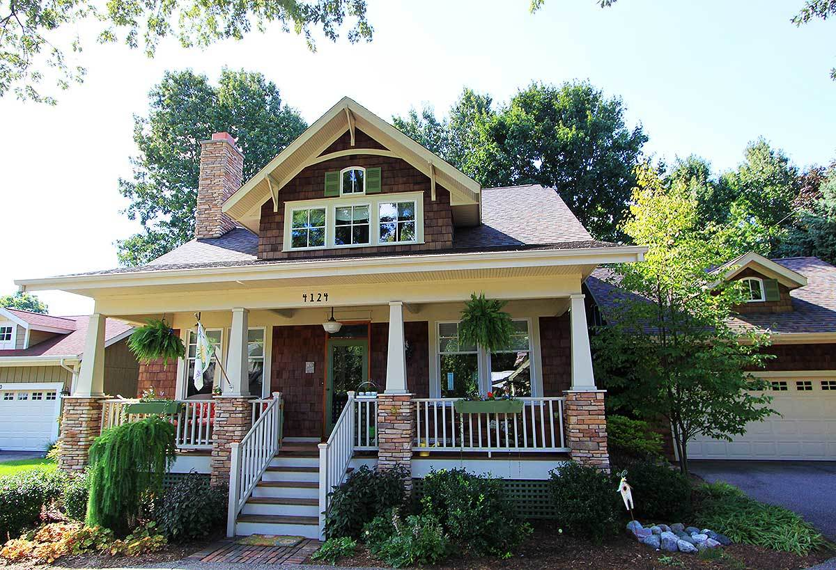 Home facade with a large dormer window, a wooden stoop, and tapered columns framing the front porch.