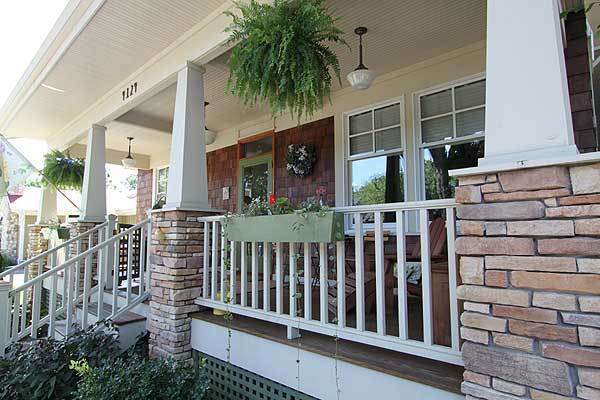 Stone columns and white wooden railings surround the front porch.