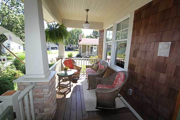 The covered front porch is furnished with a round side table and wicker round back chairs sitting on a beige area rug.