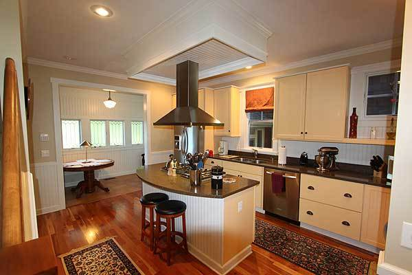 Sitting across the kitchen is the breakfast nook that features a round wooden table.