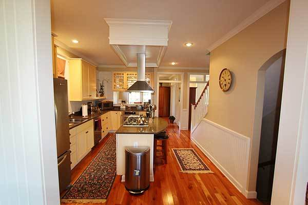 The kitchen has beige walls and a rich hardwood flooring topped with floral runners.