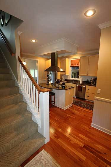 A traditional staircase near the kitchen dressed in a brown textured carpet.
