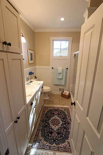 Bathroom with white vanity, a toilet, and a tasseled rug that lays on the beige tile flooring.