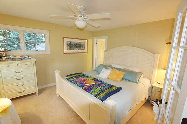 Another bedroom with white furnishings, yellow walls, and beige carpet flooring.