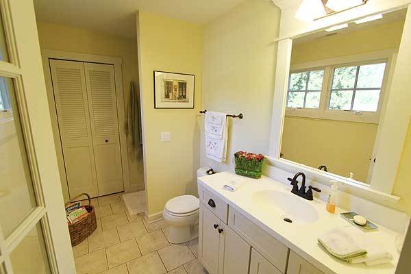 This bathroom is equipped with a toilet and a white sink vanity fitted with contrasting wrought iron fixtures.