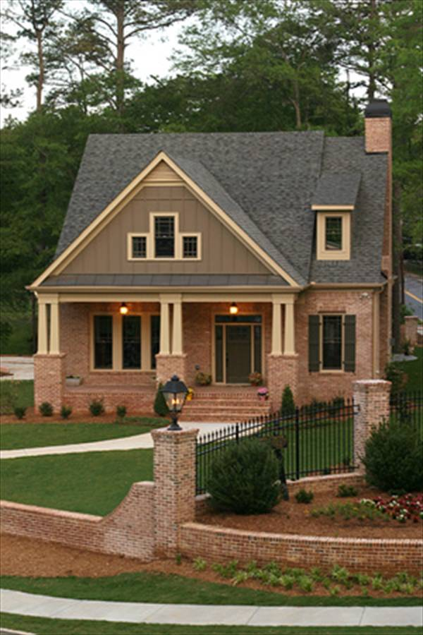 Home facade with red brick exterior and a covered porch framed with decorative columns.