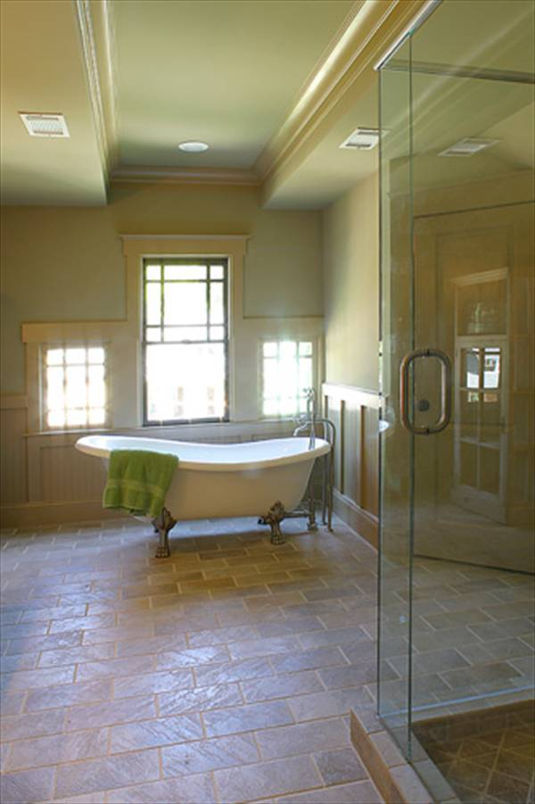 Primary bathroom with a walk-in shower and a clawfoot tub placed against the Palladian window.