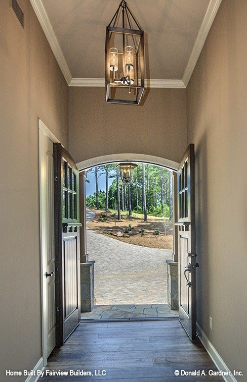 A dark wood double door opens to the foyer with wide plank flooring and gray walls lined with white moldings.