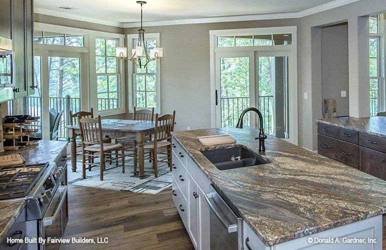 Eat-in kitchen with granite countertops and two islands where one is fitted with a double bowl sink.